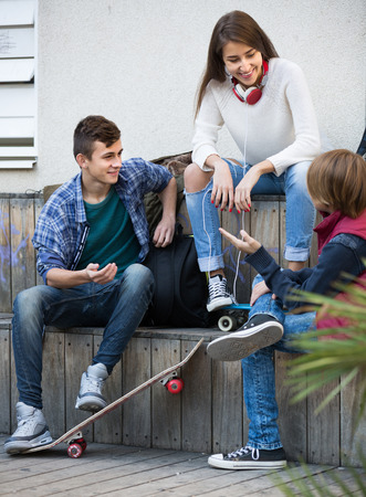 blabbing: Happy smiling three teenagers hanging out outdoors and discussing something Stock Photo