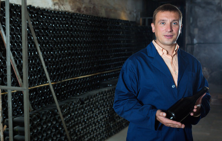 laboratorian: Glad male winery technician posing with bottle of wine in cellar