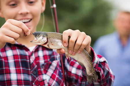 Glad teenager boy holding and looking at the fish on the hook Stock Photo