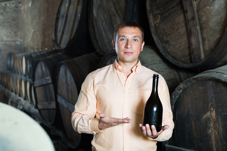 Portrait of man posing with bottle of wine in winery cellar