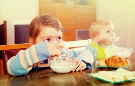 siblings: Two  siblings eating dairy breakfast together at wooden table