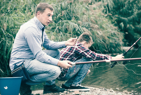 Excited adult man fishing on freshwater lake from shore on forest Stock Photo