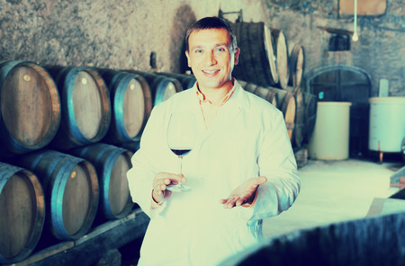 laboratorian: joyful factory sommelier in white robe checking quality of red wine in cellar with barrels