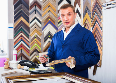 diligent: Cheerful smiling  diligent man worker holding picture frame details on counter in studio Stock Photo