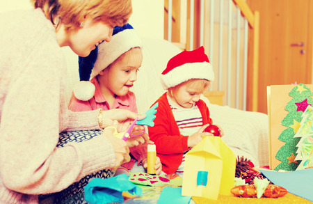 Happy woman with two daughters preparing for Christmas at home Stock Photo