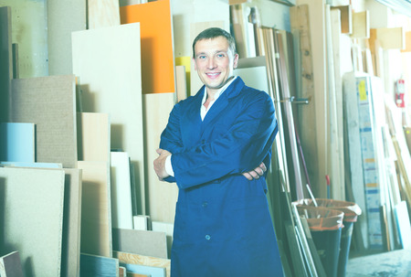 picture framing: professional workman standing with plywood pieces in picture framing workshop