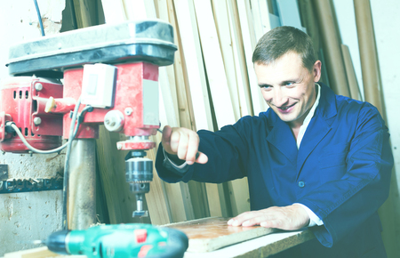 russian man: portrait of  happy russian man in uniform working with electrical screwdriver on plywood indoors