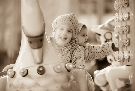 christmas grounds: Portrait of little sisters laughing at roundabout