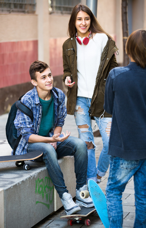 Three positive smiling teenagers in casual hanging out outdoors and discussing something . Focus on guy