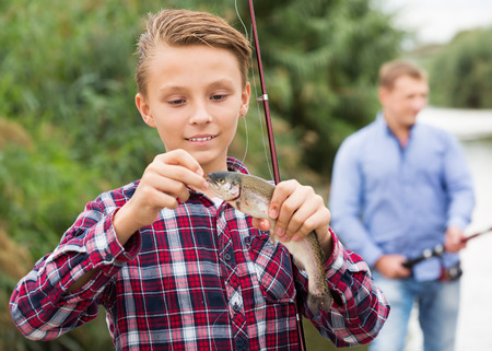Glad teenager boy holding and looking at fish on the hook Stock Photo