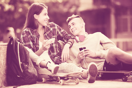 teens playing: Girl and boy teens playing on smartphones and listening to music Stock Photo