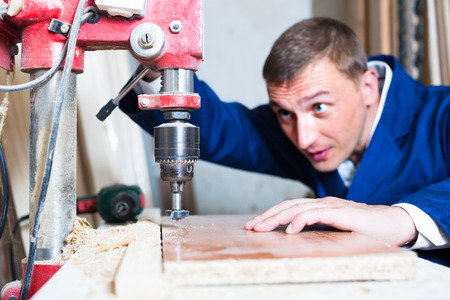 workman drilling planks using electrical screwdriver in workshop