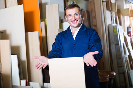 picture framing: Cheerful male worker standing with plywood pieces in picture framing workshop