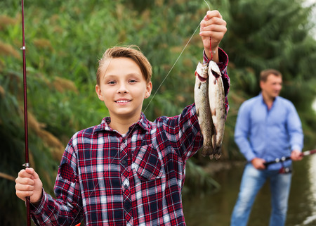 Portrait of cheerful ad teenager boy showing catch fish he holding in hands