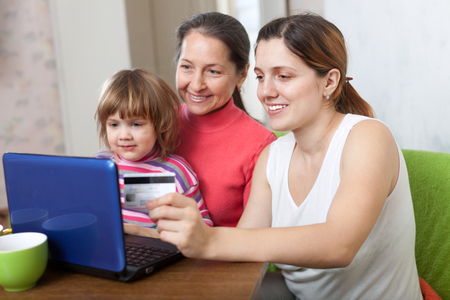 three generations: Family of three generations buying online with laptop and credit card at home Stock Photo