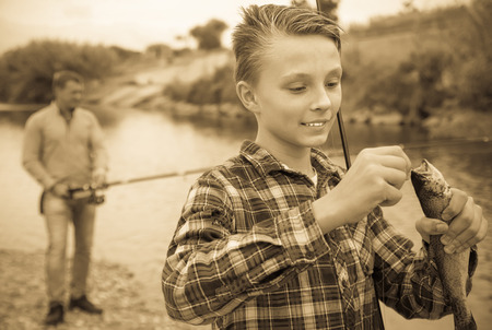 gudgeon: Positive young boy holding on hook freshwater fish on forest