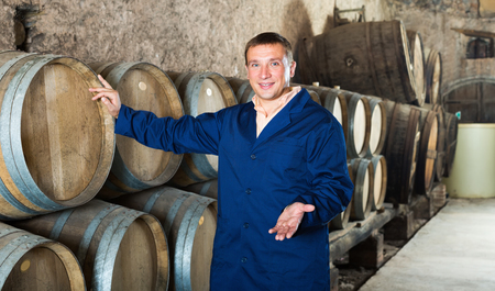 laboratorian: Man wine house technician working in storage with wooden barrels