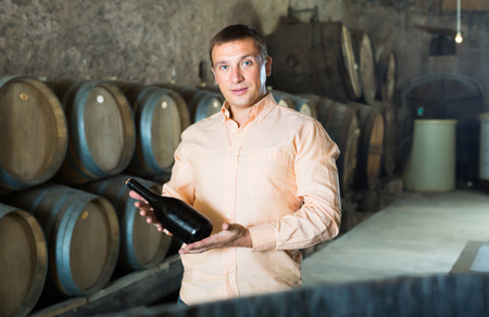 Handsome adult man posing with bottle of wine in winery cellar