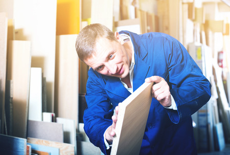 picture framing: Cheerful workman standing with plywood pieces in picture framing workshop Stock Photo