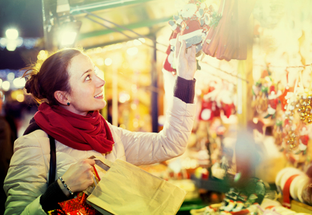 plaything: young russian girl shopping at festive fair before Xmas in evening time