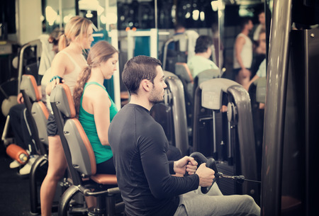 anaerobic: Group of young adults doing powerlifting on machines in fitness club Stock Photo