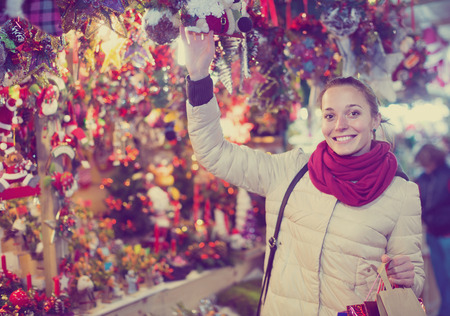 overspending: smiling  young russian woman choosing Christmas decoration at market in evening time