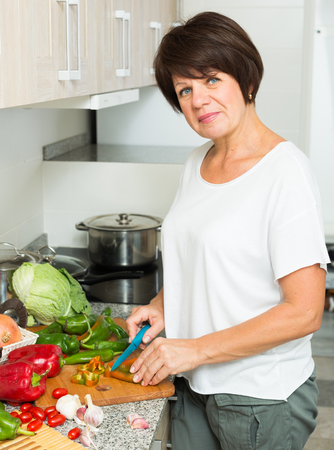 glad: glad mature woman standing at kitchen and preparing salad indoors