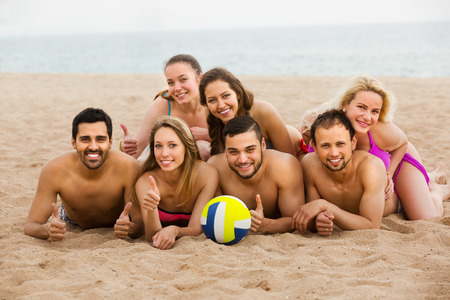 Positive young adults relaxing at sandy beach in sunny day. Selective focus