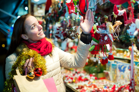 Cheerful girl customer near counter with Christmas gifts in evening time selects gifts for loved ones Stock Photo