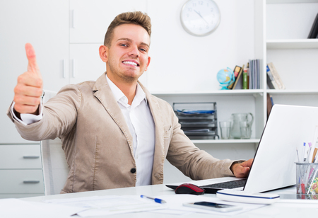 Smiling manager with thumbs up gesture at office desk