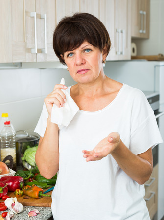 unsatisfied: negative mature woman housewife standing with napkin at her kitchen indoors