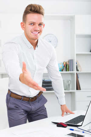 Smiling business partner welcoming somebody at desk in office Stock Photo