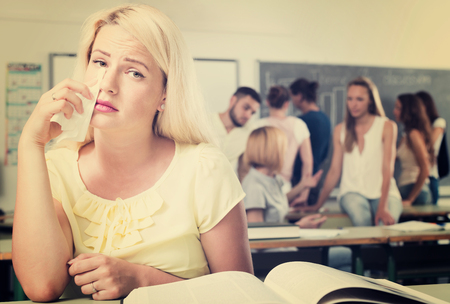 outsider: Lonely student with sad expression sits at her desk in the classroom Stock Photo