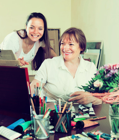 the admirer: Happy woman artist with her admirer select pictures Stock Photo