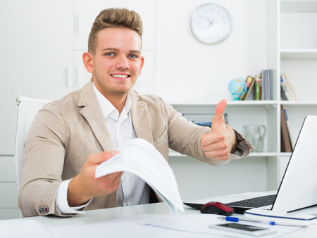 Portrait of excited businessman showing thumbs up in modern office