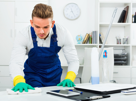 diligent: Diligent friendly male professional janitor dusting in modern office interior Stock Photo