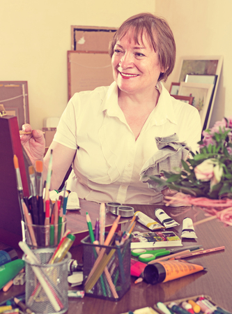 contentedness: Active senior artist in the process of creating a new picture Stock Photo