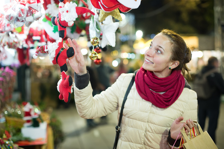 lifestile: Portrait of happy female customer at Christmas fair in evening