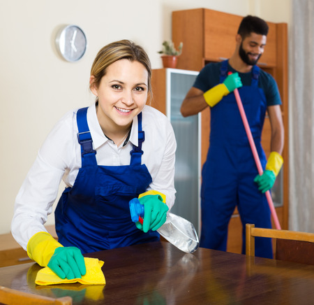office cleanup: smiling american interracial professional couple in uniform cleaning at domestic interior