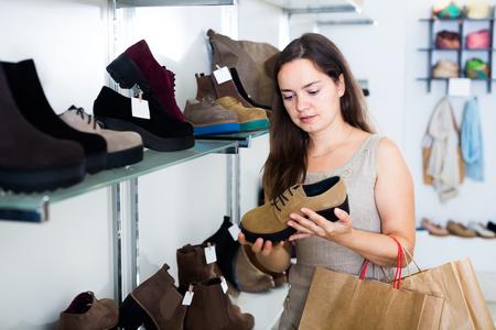 footgear: Portrait of happy woman selecting loafers in footgear center
