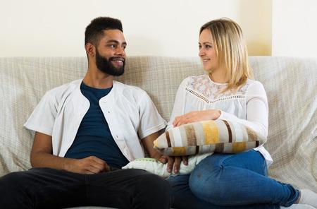 interracial couple: Young interracial couple talking in domestic interior