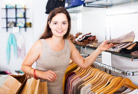comprando zapatos: Happy young brunette buying summer shoes in footwear shop Foto de archivo