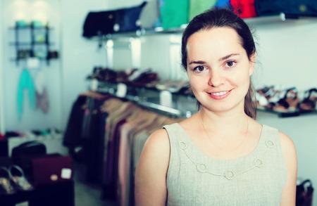 salesgirl: portrait of joyful female seller with dark hair working in shoes store