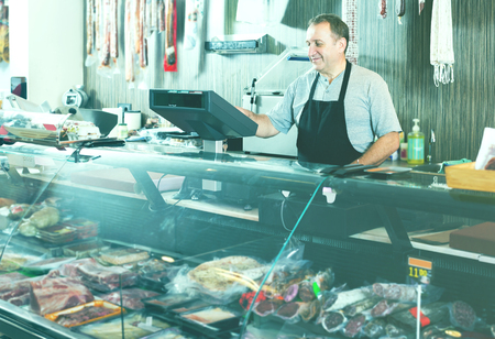 carniceria: vendedor de sexo masculino feliz que presenta con wursts en una carnicería
