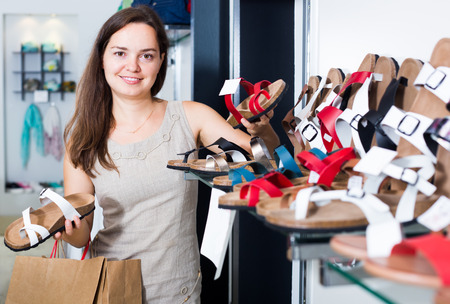 woman sandals: cheerful smiling young woman choosing summer sandals in shoes store   Stock Photo