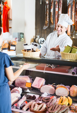 25s: Mature american salesman offering sausages to young woman in delicatessen shop