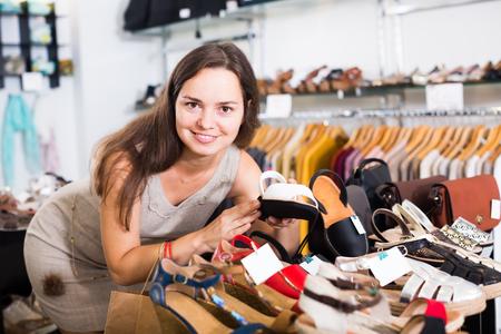 footgear: Portrait of happy female customer selecting shoes in footgear center Stock Photo