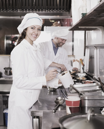 shef: portrait smiling female cook cooking at professional kitchen in the take-away  restaurant
