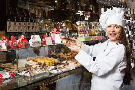 shopgirl: Cheerful young shopgirl posing with different chocolate and confectionery at display Stock Photo