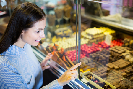 patty cake: Smiling woman selecting fine chocolates and confectionery at cafe display